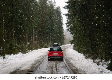 Красный автомобиль с багажниками, едет по лесной дороге зимой, сильный снегопад. Понятие путешествия на автомобиле