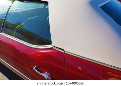 Red car side view with white roof and chrome handle