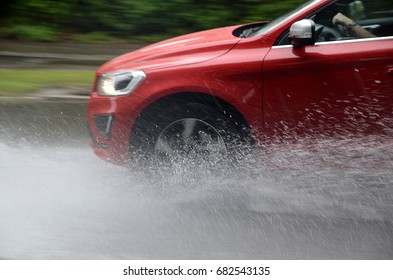 A red car splashes trough water on a partly flooded road.