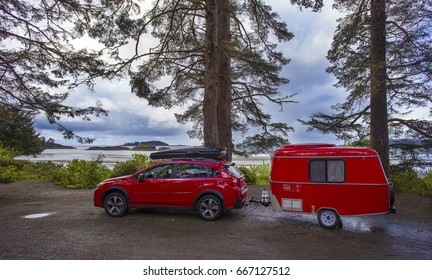 RED CAR WITH TINY CAMPER TRAILER CAMPING IN VANCOUVER ISLAND, BRITISH COLUMBIA, CANADA - May 10, 2017: Camping with tiny trailer, Vancouver Island