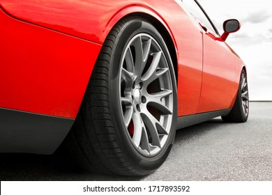 Red car. Car wheels close up on a background of asphalt. Car tires. Car wheel close-up. for advertising.