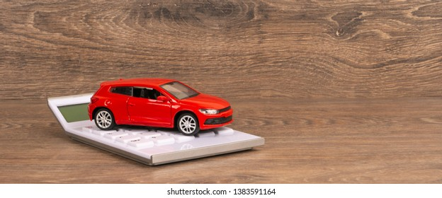 red car and white calculator on wooden table, panoramic shot