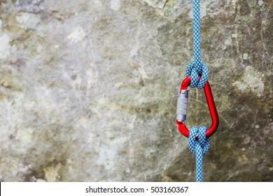 Red carabiner with climbing rope on rocky background. Climbing concept