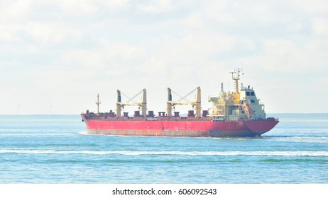 Red cargo ship (bulk carrier) sailing by the coast of Vlissingen, the Netherlands