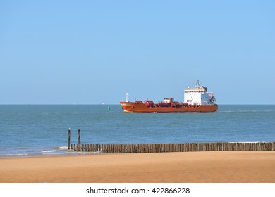 Red cargo tanker ship sailing next to the coast of Vlissingen, the Netherlands