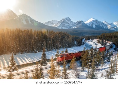 Red cargo train passing through Morant's curve in Bow Valley, Banff National Park, Alberta, Canada. Rocky Mountains of North America. Beautiful snowy winter scenery in background with lens reflection.