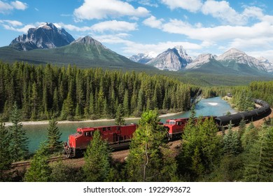 Red cargo train passing through Morant's curve in Bow Valley, Banff National Park, Alberta, Canada. Iconic landscape and railway system in the Rocky Mountains of North America.