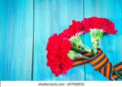 Red carnations tied with Saint George ribbon on gray.