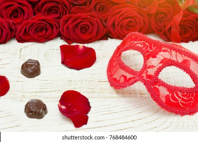 Red carnival mask and candy on a wooden table, scarlet roses on a background