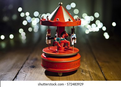 Red carousel toy with blur lights background. Grain and selective focus.