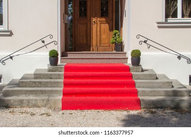 a red carpet on the entrance steps of a house leads to the front door