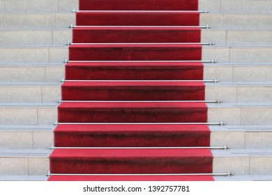 Red carpet on staircase outside leading to building entrance