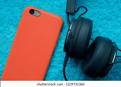 Red case smartphone with camera side up next to black headphones on a shabby fabric