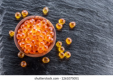 Red caviar in the bowl on gray graphite background. Macro picture.