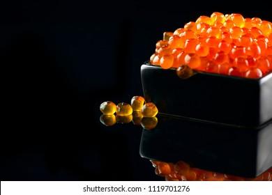 Red Caviar. Caviar in bowl over black background. Close-up salmon caviar. Delicatessen. Gourmet food. Texture of caviar. Seafood