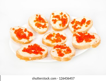 Red caviar on bread with butter on white plate closeup