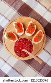 Red caviar sandwiches on plate on wooden background