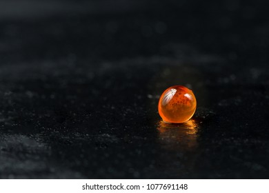 Red caviar. Single fish egg on dark stone background.