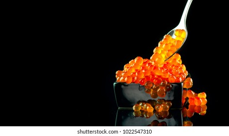 Red Caviar in a spoon. Caviar in bowl over black background. Close-up salmon caviar. Delicatessen. Gourmet food. Texture of caviar. Seafood.