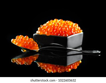 Red Caviar in a spoon. Caviar in bowl over black background. Close-up salmon caviar. Delicatessen. Gourmet food. Texture of caviar. Seafood.