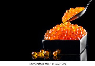 Red Caviar in a spoon. Caviar in bowl over black background. Close-up salmon caviar. Delicatessen. Gourmet food. Texture of caviar. Seafood