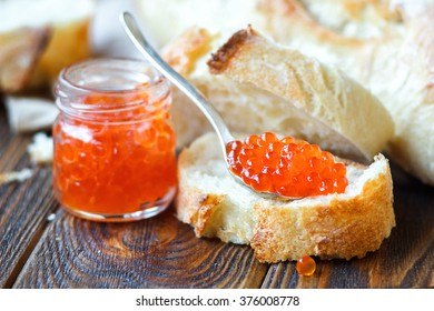 Red caviar in spoon with white bread on wooden background. Selective focus.