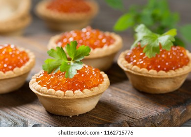 Red caviar in tartlets on a wooden table