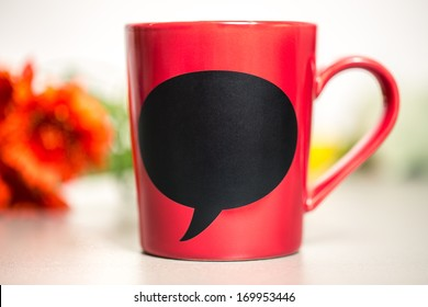 Red ceramic cup with empty chalk board. Standing on a kitchen table.