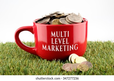 Red ceramic cup written Multi Level Marketing with coins inside, finance conceptual.