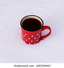 red ceramic mug with white circles with black coffee on the white snow, top view
