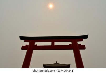 The red ceremonial pillars, see the brown roof under the double red pillars, see the sun above the pillars.