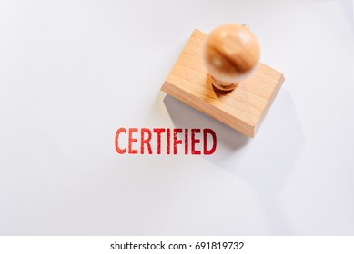 Red certified rubber stamp on white sheet of paper. Law office.