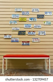 Red chair collection of old vintage license plates on a wood wall background