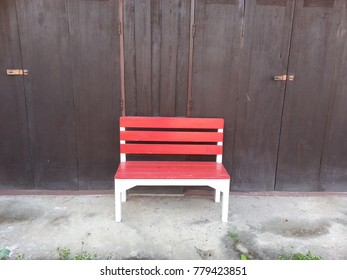 Red chair In front of old wooden doors.