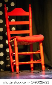 A red chair on stage for use of the dancers in a Flamenco show in Seville, Spain