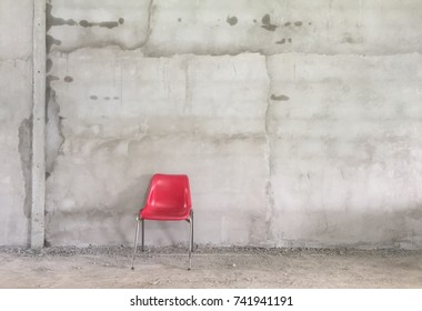 Red chair with retro cement walll background and copy space your text design.