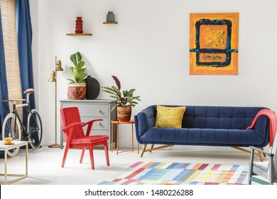 Red chair and royal blue lounge placed in bright sitting room interior with colorful carpet, modern art painting, fresh plants and gold lamp next to grey cupboard