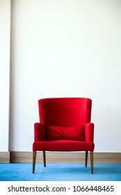 Red chair in white wall interior with blue wood flooring.
