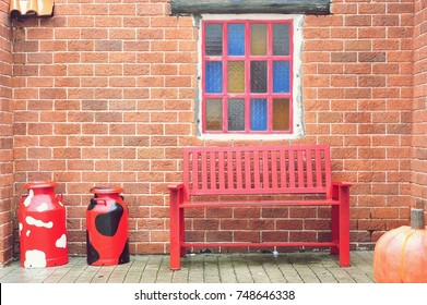 Red chairs with brick wall in backyard.