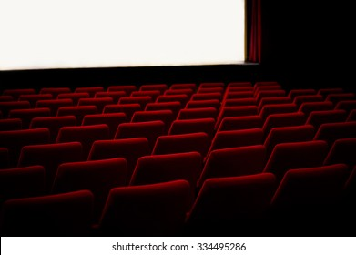 Red chairs in empty cinema theater with empty stage. Light illumination of the stage. Soft light.