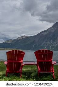 Red Chairs Look Over Waterton Lake from grassy lawn