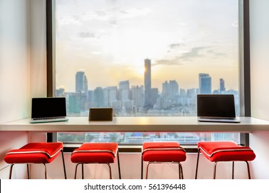 Red chairs in modern design arranged by a long wall mounted table with laptops and tablets laid on top. They are set by the window - a metaphor for co-working space, startup, IT project, and teamwork.
