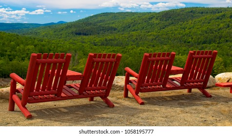 Red chairs on a scenic overlook viewing the western mountains of Maine