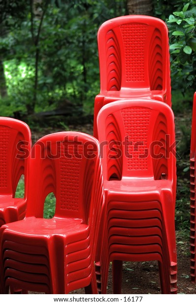 Red chairs stacked out on a cloudy monsoon day