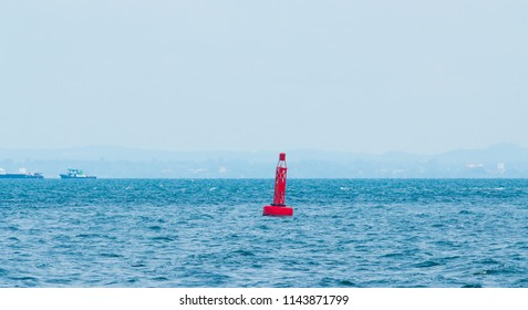 Red channel marker buoy floating in the sea.
