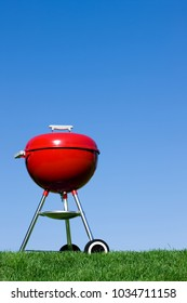 Red charcoal grill against a clear blue summer sky Vertical