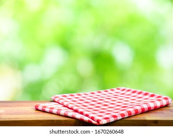 Red checked tablecloth on wood with blur green bokeh of tree background.Summer and picnic concepts.Design for key visual food and drink products.no people