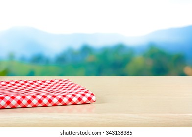 Red checkered cloth on wood table top in blur mountain background - can be used for display or montage your products
