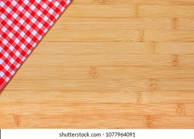 Red checkered cloth on a wooden surface. Dining napkin. Kitchen towel