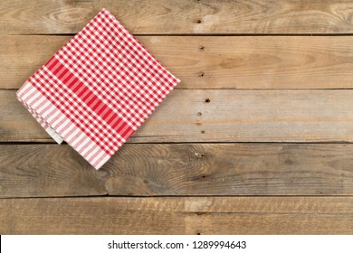 Red checkered dishcloth on brown rustic wooden plank table flat lay top view from above with copy space